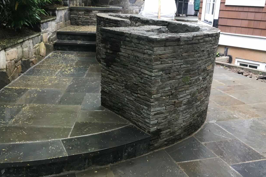 Stone paver patio with stairs and walls