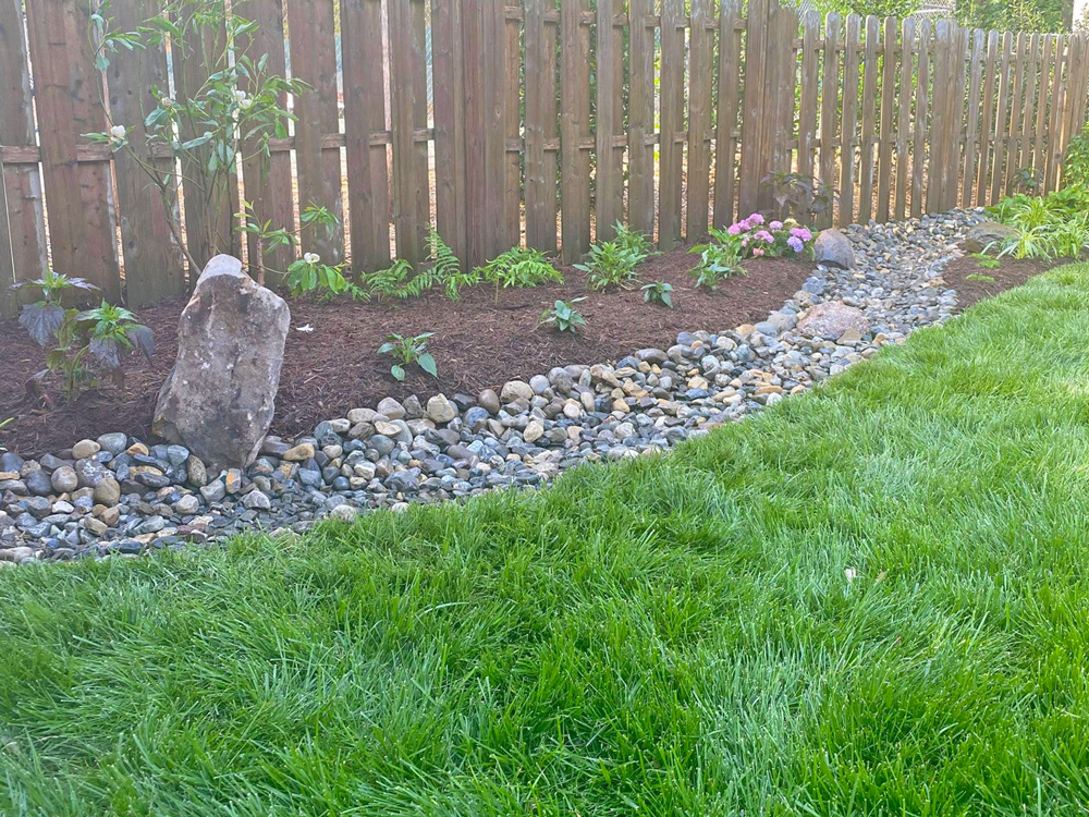 Drainage fix with stone and plants against fence