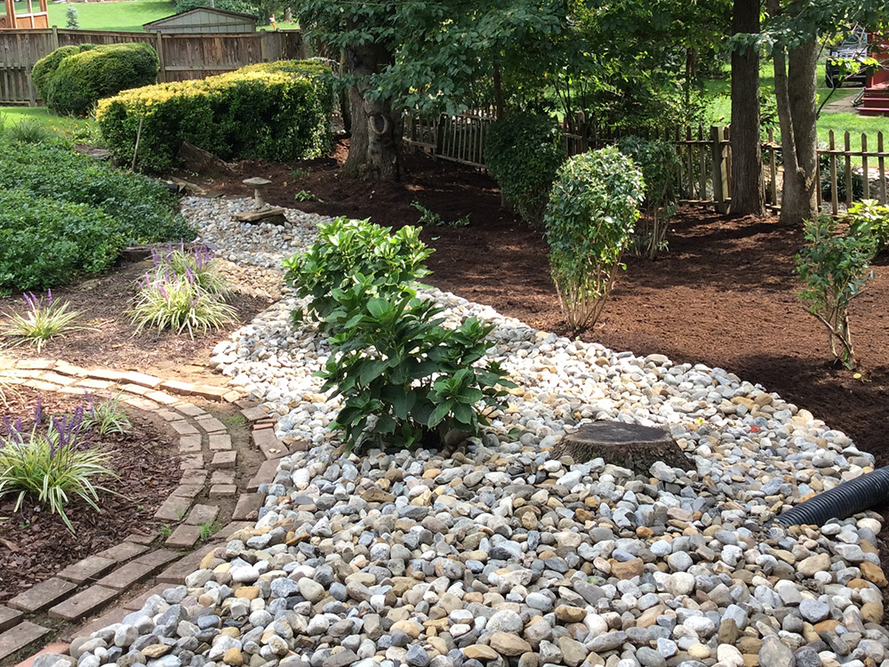 drainage fix with river rock and plant installation