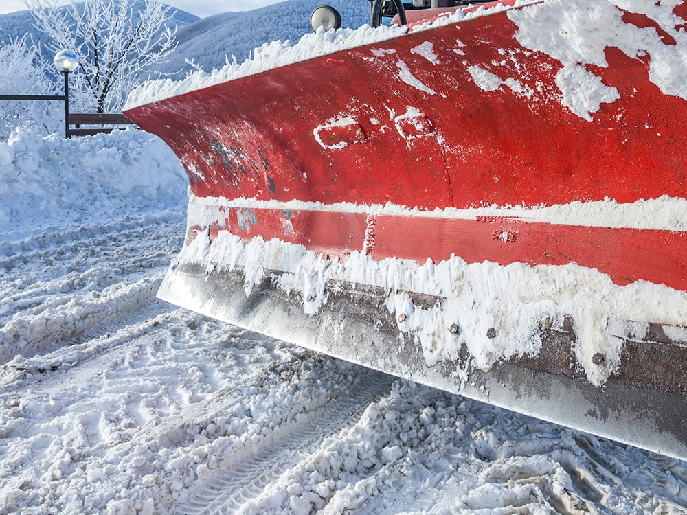 Red plow in snow plowing snow